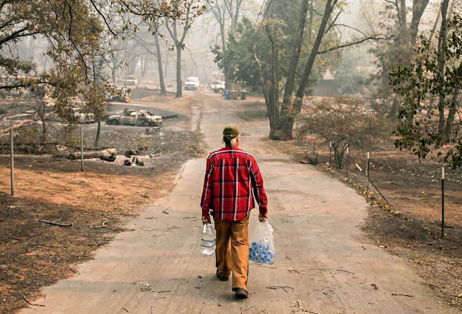 Brad Weldon carries water dropped off by passerbys back to his home, through his neighborhood that was destroyed after the Camp Fire devastated the entire town of Paradise, Calif. Saturday, Nov. 10, 2018. Weldon stayed in his home with his 90-year-old mother, Norma Weldon, and roommate, Mic McCrary, as the fire overtook their entire neighborhood while leaving his home untouched. Photo: Jessica Christian / The Chronicle