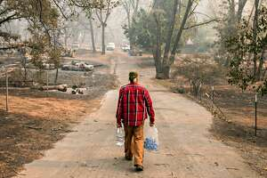 Brad Weldon carries water dropped off by passerbys back to his home, through his neighborhood that was destroyed after the Camp Fire devastated the entire town of Paradise, Calif. Saturday, Nov. 10, 2018. Weldon stayed in his home with his 90-year-old mother, Norma Weldon, and roommate, Mic McCrary, as the fire overtook their entire neighborhood while leaving his home untouched.