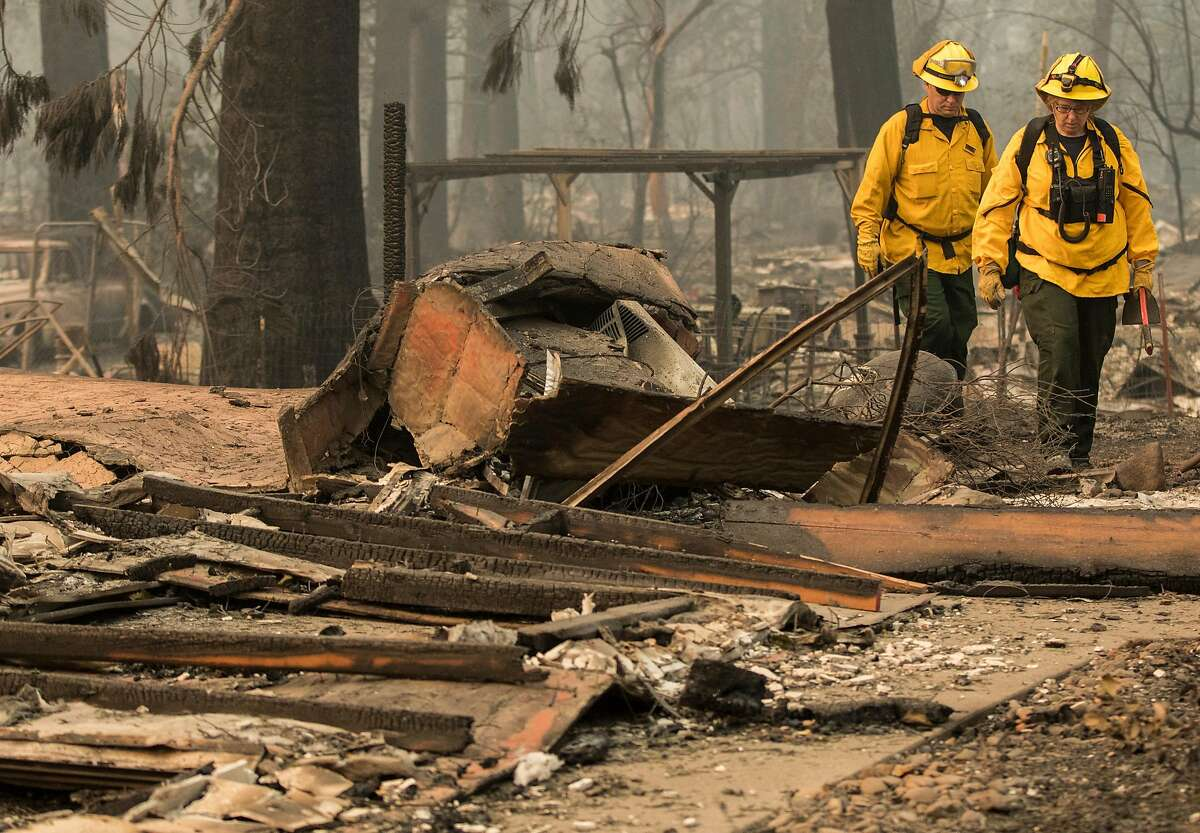 Firefighters walk through a charred neighborhood off Billie Road after the Camp Fire devastated the entire town of Paradise, Calif. Saturday, Nov. 10, 2018.