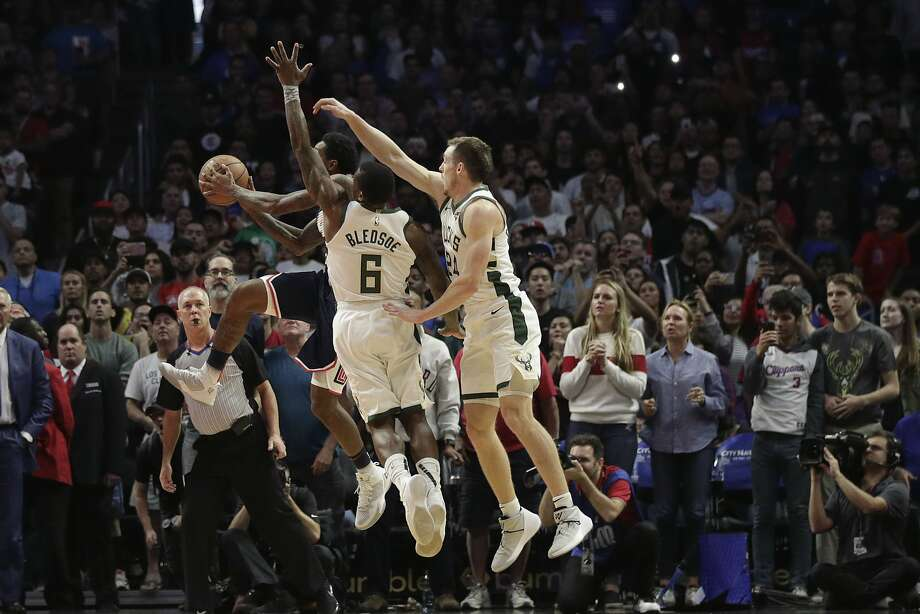 Lou Williams goes up for the winning shot against Milwaukee's Eric Bledsoe and Pat Connaughton with less than 2 second left in overtime. Photo: Jae C. Hong / Associated Press