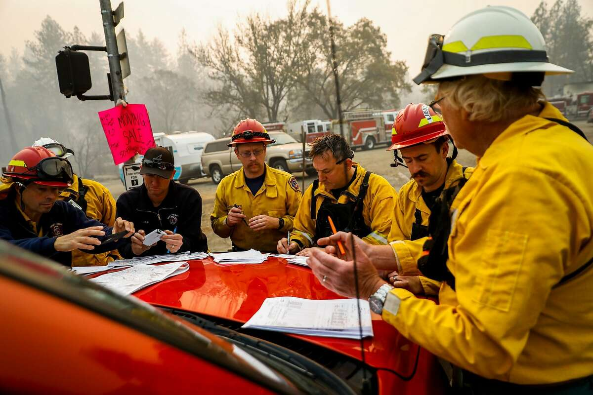 Firefighters get ready for the day as they have a meeting on Skyway after the Camp Fire tore through Paradise, Calif. on Saturday, Nov. 10, 2018.