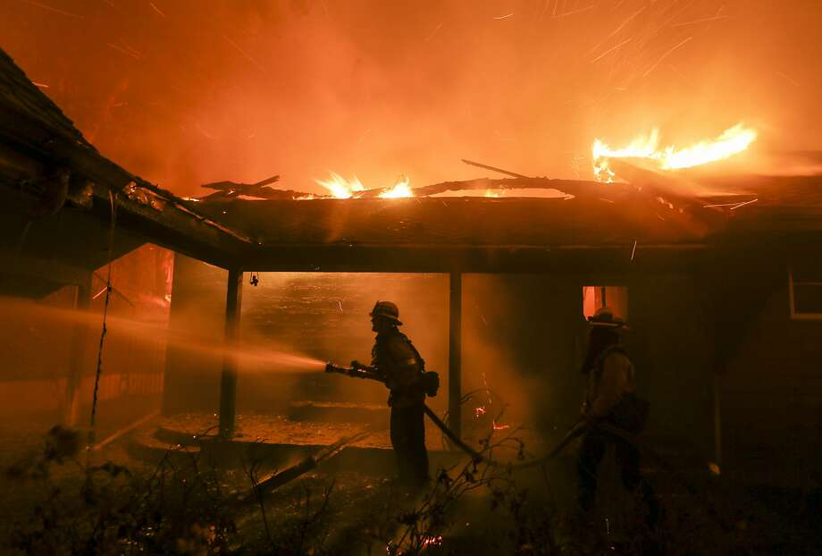 Firefighters battle the Woolsey Fire burning a home in Malibu, Calif., Friday, Nov. 9, 2018. A Southern California wildfire continues to burn homes as it runs toward the sea. But winds that drove the ferocious flames have eased Friday night, but are expected to return Sunday.  Photo: Ringo H.W. Chiu / Associated Press