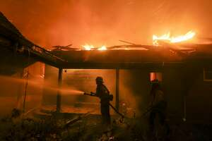 Firefighters battle the Woolsey Fire burning a home in Malibu, Calif., Friday, Nov. 9, 2018. A Southern California wildfire continues to burn homes as it runs toward the sea. But winds that drove the ferocious flames have eased Friday night, but are expected to return Sunday.  (AP Photo/Ringo H.W. Chiu)