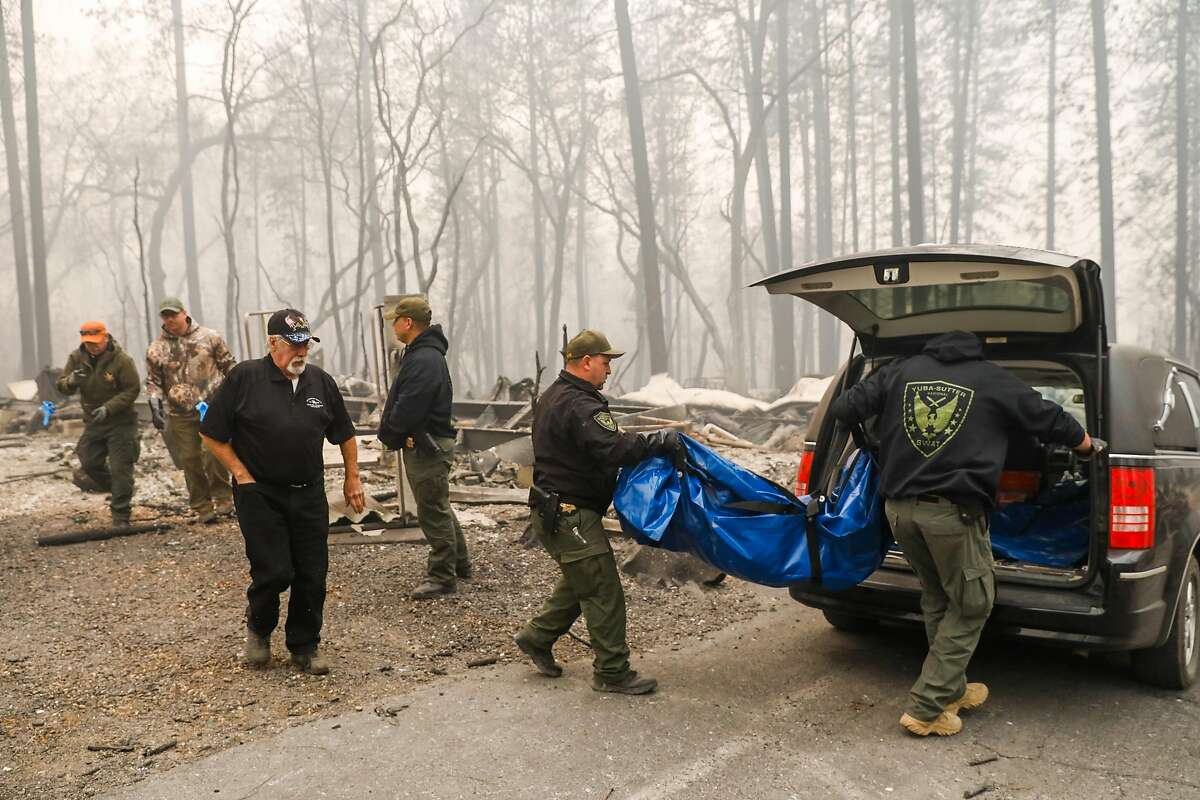 Yuba County Sheriffs carry a body bag into a hearse after discovering a fatality following the Camp Fire in Paradise, California, on Saturday, Nov. 10, 2018.