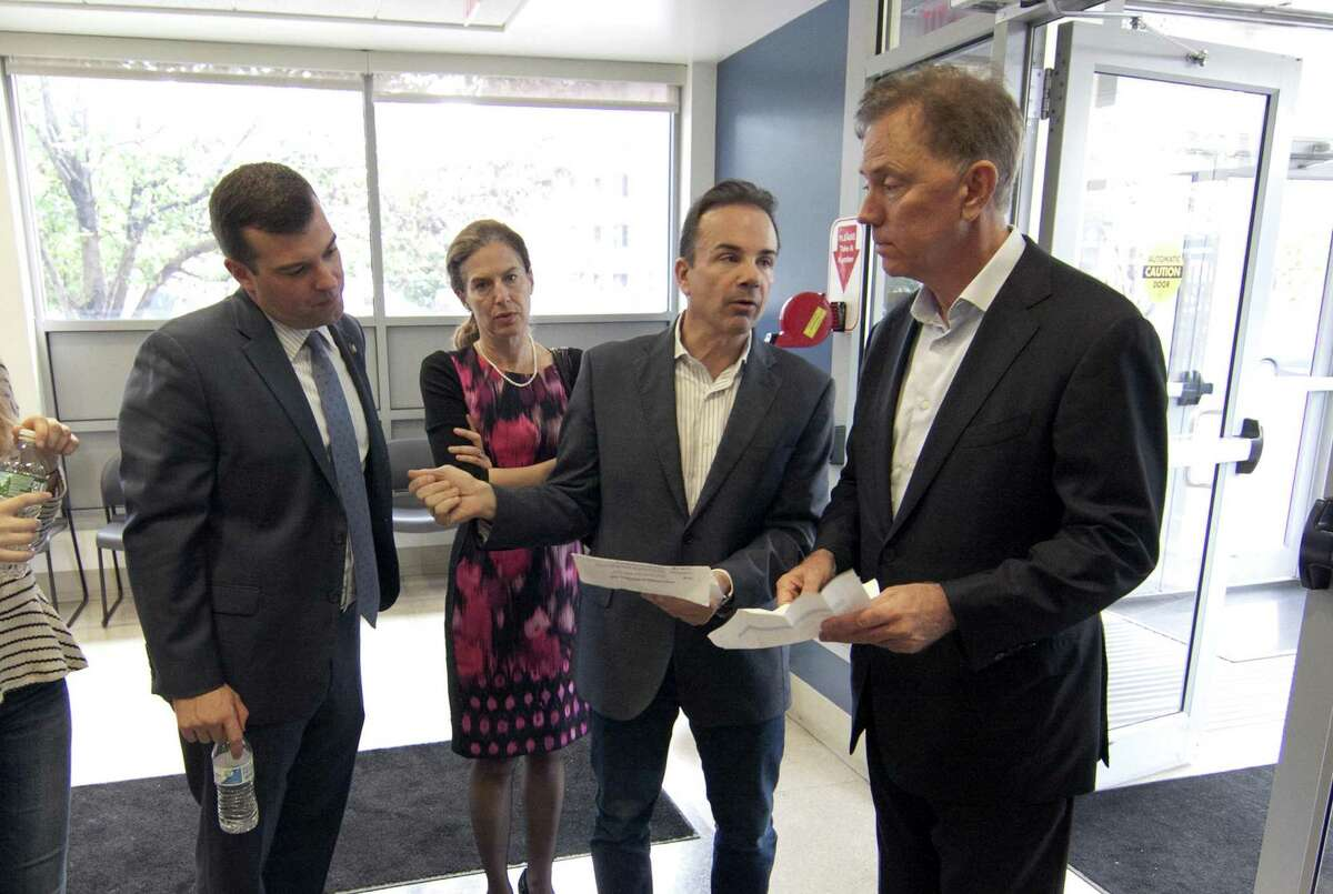 State Representative Steve Stafstrom, left, and Lt. Governor candidate Susan Bysiewicz look on as Democratic gubernatorial candidate Ned Lamont, at right, confers with Bridgeport Mayor Joe Ganim after visiting the Southwest Community Health Center in Bridgeport, Conn., on Saturday, Nov. 1, 2018. An open enrollment press conference was held at the center with Lamont, U.S. Senator Chris Murphy, Bysiewicz, Mayor Ganim and other state lawmakers.