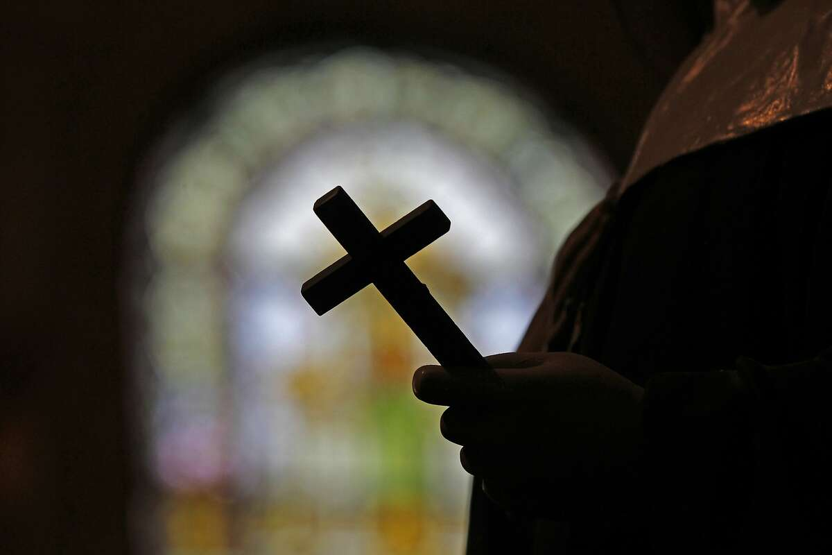 FILE - This Dec. 1, 2012 file photo shows a silhouette of a crucifix and a stained glass window inside a Catholic Church in New Orleans. As U.S. Catholic bishops gather for an important national assembly, the clergy sex abuse crisis dominates their agenda. But it's only one of several daunting challenges facing the nation's largest religious denomination. While federal and state law enforcement agencies widen their investigations of abuse, the church finds itself with ever fewer priests and nuns in service. (AP Photo/Gerald Herbert)