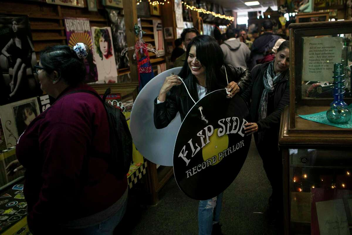 In this Nov. 2018 photo, Clarisa Peña grins as she puts on a sandwich board bearing the Flip Side Record Parlor logo during a benefit held to support her as she battled cancer for the second time in three years. Peña died Jan. 13, 2020 from cancer at age 46.