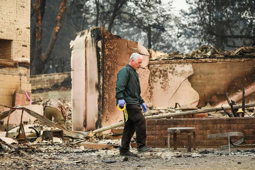 A Butte County Sheriff looks for fatalities following the Camp Fire in Paradise, California, on Saturday, Nov. 10, 2018.