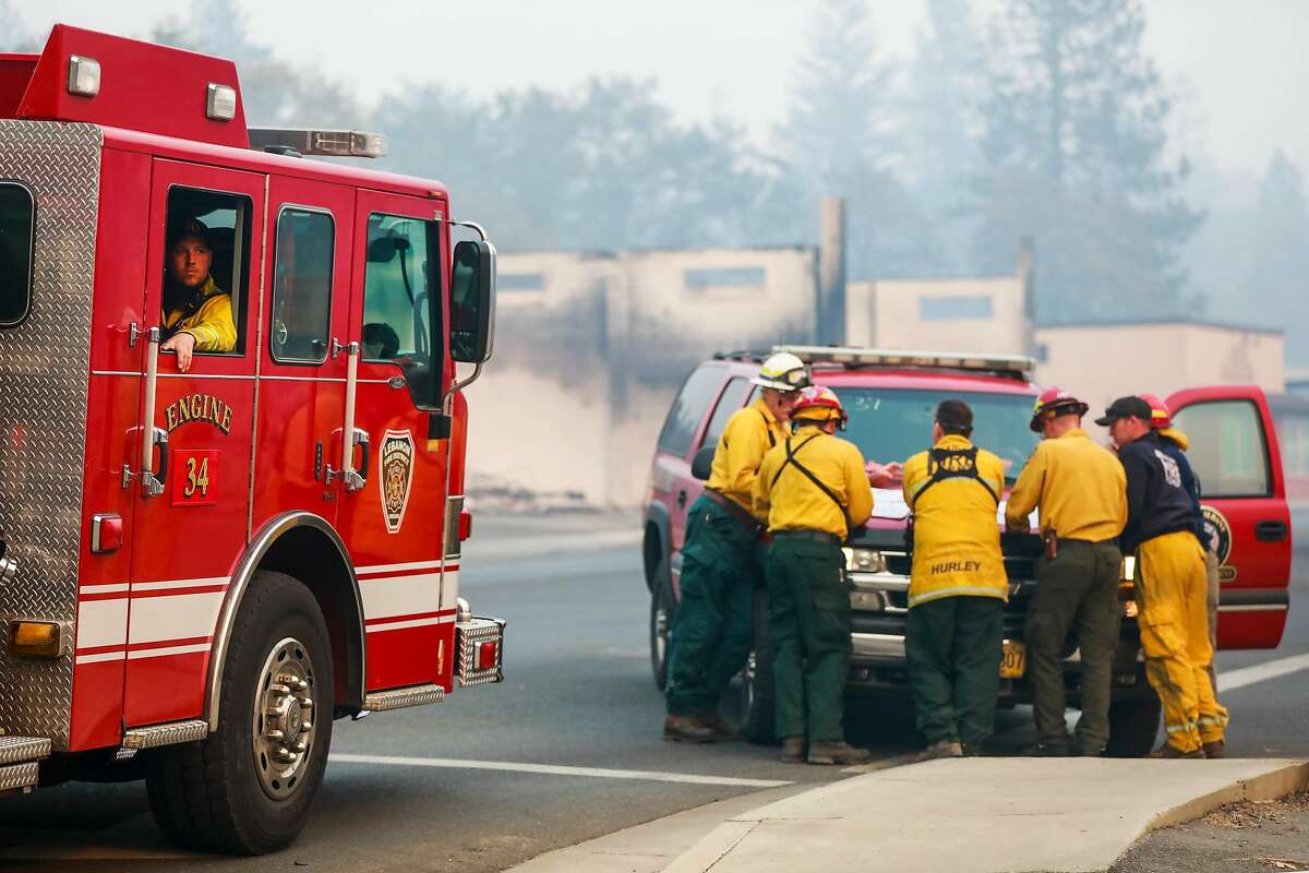 Firefighter Nick Unruh sits in his engine as others have a meeting on Skyway after the Camp Fire tore through Paradise, Calif. on Saturday, Nov. 10, 2018.