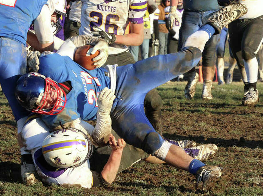 Carlinville receiver Jake Ambuel (top) is dragged to the ground by a Williamsville defender after making one of his 12 catches in the Cavaliers' 35-21 Class 3A quarterfinal victory Saturday afternoon in Carlinville. Ambuel's catch total was one shy of the 3A playoff record. Photo: Greg Shashack / The Telegraph