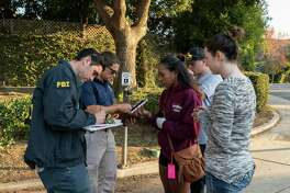 Jasmine Alexander, 25, center, speaks to an FBI agent Friday to recover her car, which she left near Borderline Bar and Grill in Thousand Oaks, California. Alexander was in the bar Wednesday during the mass shooting. She hurt her left hand while climbing out of a window.