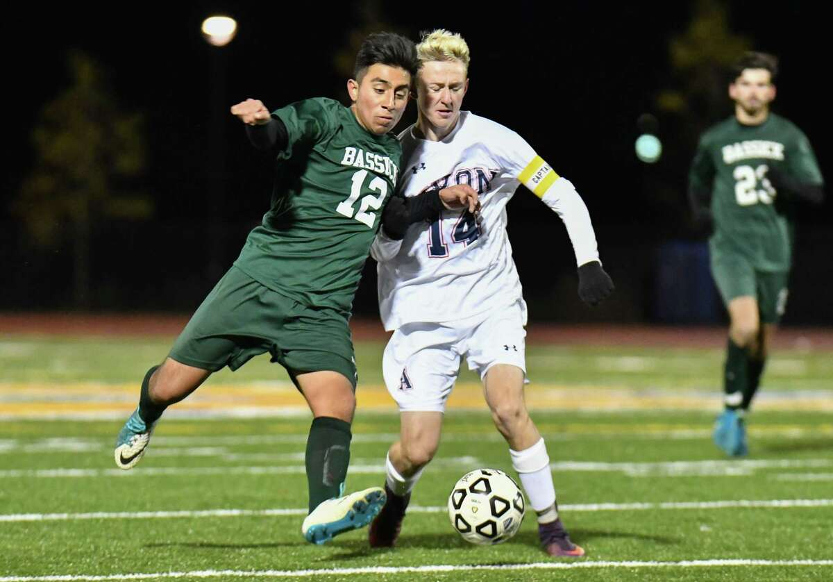 Christian Barrales (12) of the Bassick Lions and Alex Rostenberg (14) of the Avon Falcons battle for control during a CIAC Class L quarterfinal game played on Saturday November 10, 2018 at Harding High School in Bridgeport, Connecticut.