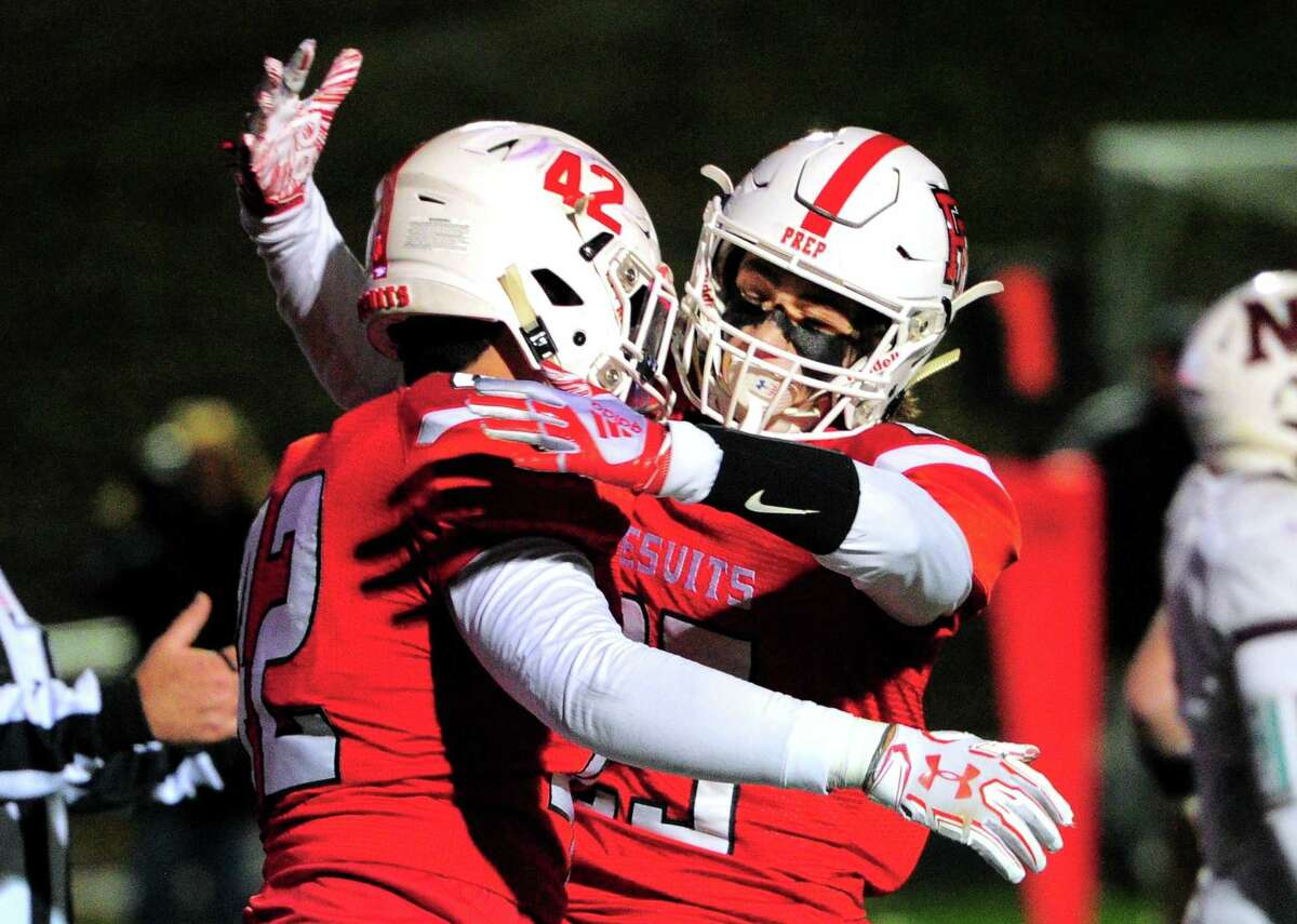 Fairfield Prep's Max McGillicuddy (25) , right, embraces teammate Zachary Sheehan (42) after Sheehan scored a touchdown during football action against North Haven in Fairfield, Conn., on Saturday Nov. 10, 2018.