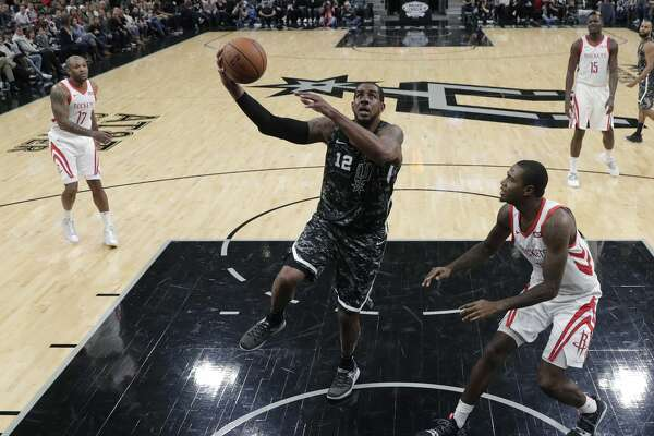 San Antonio Spurs forward LaMarcus Aldridge (12) drives to the basket past Houston Rockets forward Gary Clark (6) during the second half of an NBA basketball game, Saturday, Nov. 10, 2018, in San Antonio. (AP Photo/Eric Gay)