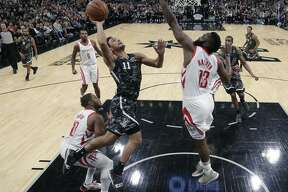 San Antonio Spurs guard Bryn Forbes (11) drives to the basket against Houston Rockets guard James Harden (13) during the second half of an NBA basketball game, Saturday, Nov. 10, 2018, in San Antonio. (AP Photo/Eric Gay)