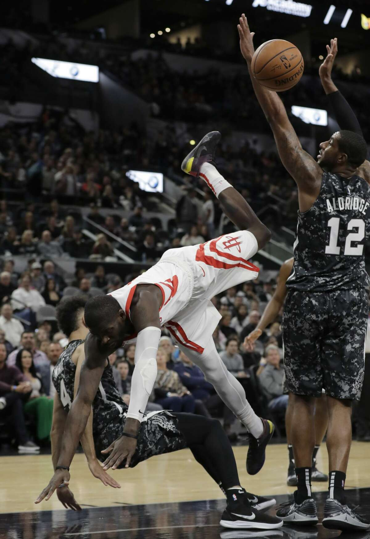 Houston Rockets forward James Ennis III, center, is upended as he tries to shoot over San Antonio Spurs guard Derrick White (4) during the first half of an NBA basketball game, Saturday, Nov. 10, 2018, in San Antonio. (AP Photo/Eric Gay)