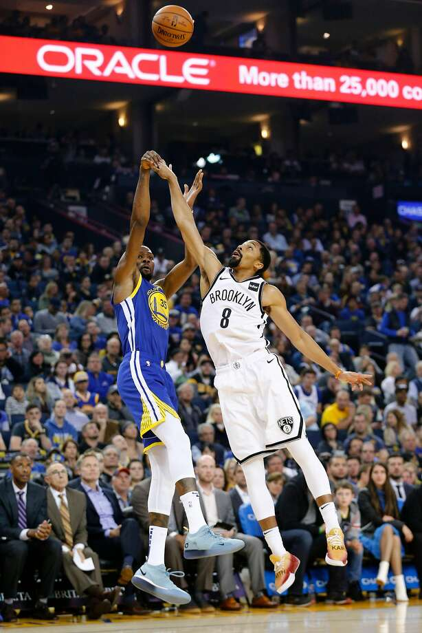 Warriors forward Kevin Durant (35) makes a shot while defended by Brooklyn guard Spencer Dinwiddie during the second half at Oracle Arena. Photo: Santiago Mejia / The Chronicle