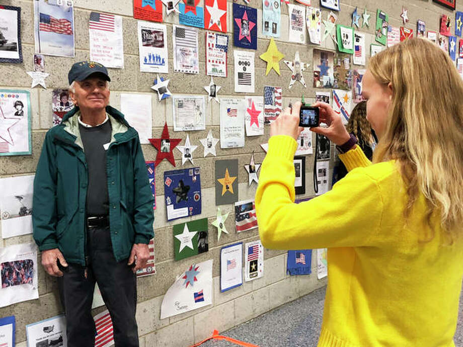 Liberty Middle School eighth-grade student Adelaide Fensterman (right) takes a photo of her neighbor Leroy Liske, a veteran, in front of the Veterans' Walking Museum at the school's Veterans Day Breakfast event Friday. Photo: Julia Biggs | The Intelligencer