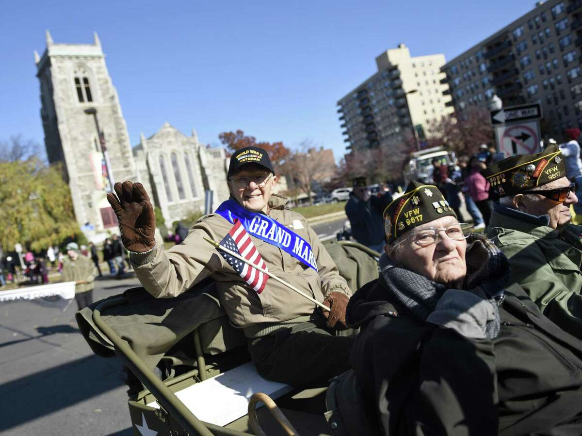 Army aircraft mechanic and flight engineer Sgt. Ted Ogonek, 92, waves to the crowd as grand marshal in the annual Stamford Veteran's Day Parade, commemorating 100 years since the end of WWI, in Stamford on Sunday.