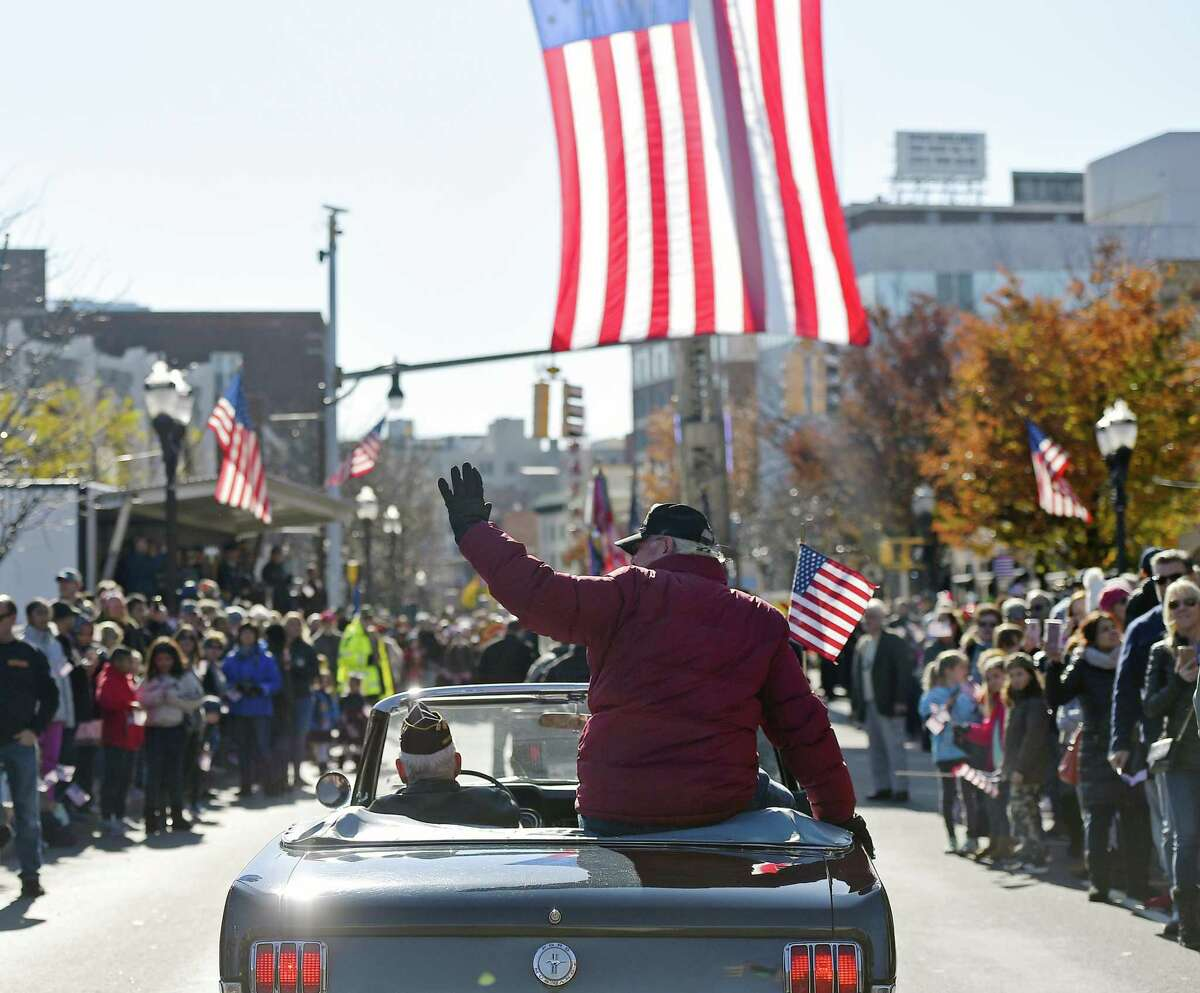Sgt. Alan Sosnowitz, a Vietnam Army veteran, waves to the crowd in the annual Stamford Veteran's Day Parade, commemorating 100 years since the end of WWI on Sunday.