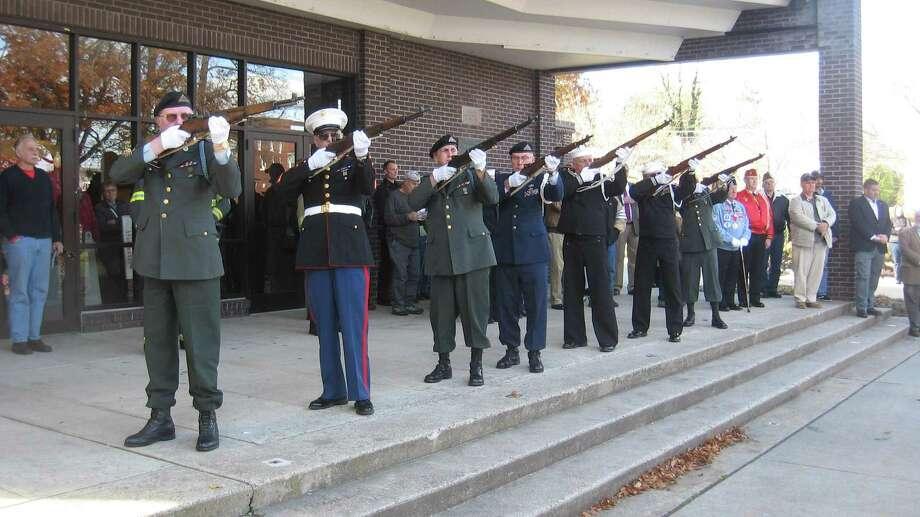 An honor guard fires a 21-gun salute. Photo: John Torsiello / Hearst Connecticut Media