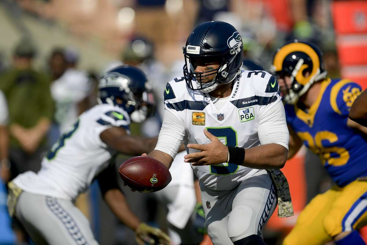 Seattle Seahawks quarterback Russell Wilson hands off against the Los Angeles Rams during the first half in an NFL football game Sunday, Nov. 11, 2018, in Los Angeles. (AP Photo/Mark J. Terrill)
