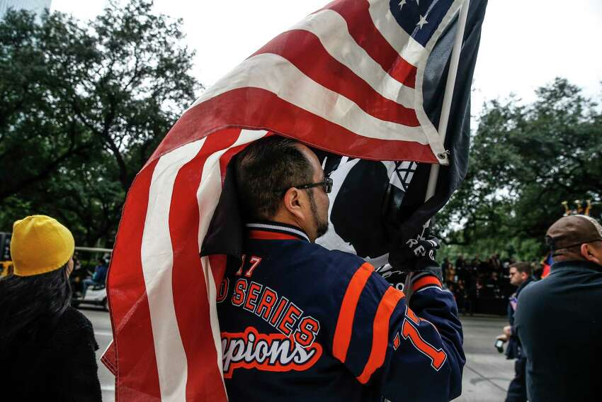 Octavio Silva gets wrapped in an American flag as he watches the Houston Salutes American Heroes Veterans Day parade Sunday, Nov. 11, 2018, honoring the 100th anniversary of the signing of the World War I Armistice.
