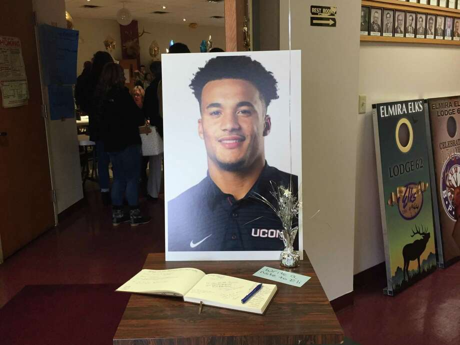 """A poster of Eli Thomas in his blue UConn shirt and a piece of paper with the words """"write a note to Eli"""" rest next to a guestbook during a fundraiser in Elmira, N.Y. on Sunday. Photo: Jim Fuller / Hearst Connecticut Media"""