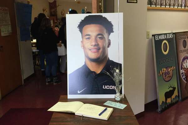 "A poster of Eli Thomas in his blue UConn shirt and a piece of paper with the words ?""write a note to Eli?"" rest next to a guestbook during a fundraiser in Elmira, N.Y. on Sunday."