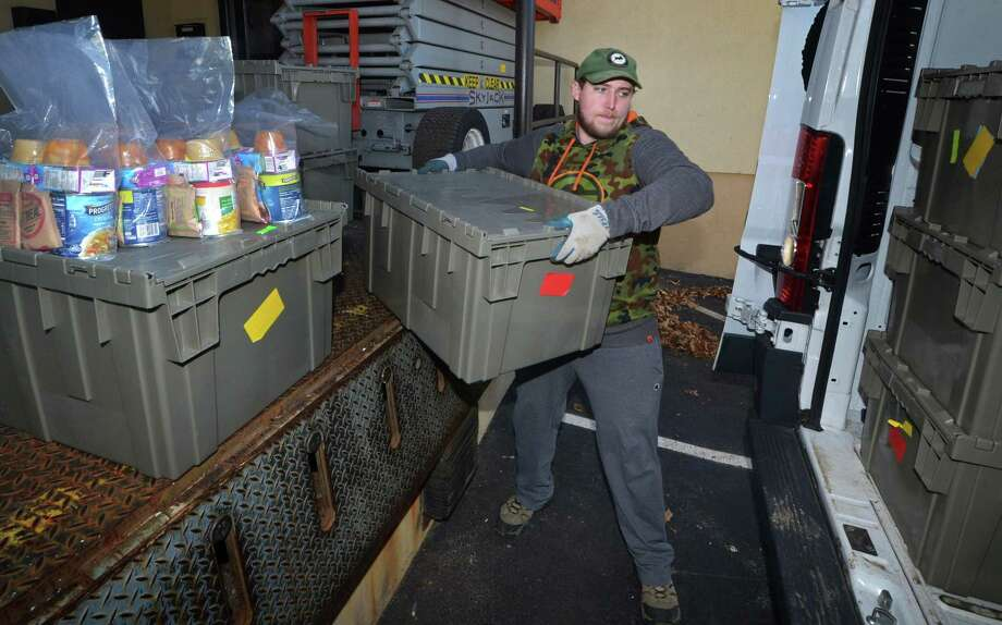 Hunter Van Veghel, delivery driver for Filling in the Blanks, loads up his truck on Thursday at their Main Avenue location in Norwalk. Filling In The Blanks is a nonprofit that fights against childhood hunger by bringing food to schools. The meals are held by social workers or teachers until Friday afternoon and then given to students who need something to eat on the weekends. Photo: Erik Trautmann / Hearst Connecticut Media / Norwalk Hour