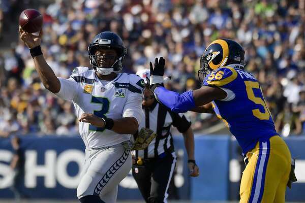 Seattle Seahawks quarterback Russell Wilson passes under pressure from Los Angeles Rams defensive end Dante Fowler during the first half in an NFL football game Sunday, Nov. 11, 2018, in Los Angeles. (AP Photo/Mark J. Terrill)