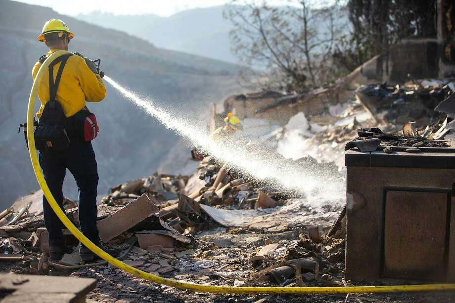 Firefighters work to put out hot spots around structures destroyed by the Woolsey Fire, which has burned more than 130 square miles in parts of Los Angeles County and Ventura County. Photo: Kent Nishimura / Los Angeles Times
