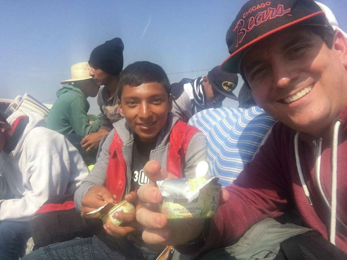 San Antonio clergyman Gavin Rogers shared a meal with a Central American youth on the caravan over the weekend as they rode atop a flatbed trailer whose driver offered a free lift to the travelers.