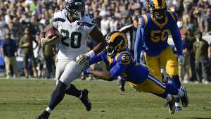 Seattle Seahawks running back Rashaad Penny, left, scores past Los Angeles Rams inside linebacker Cory Littleton during the first half in an NFL football game Sunday, Nov. 11, 2018, in Los Angeles. (AP Photo/Mark J. Terrill)
