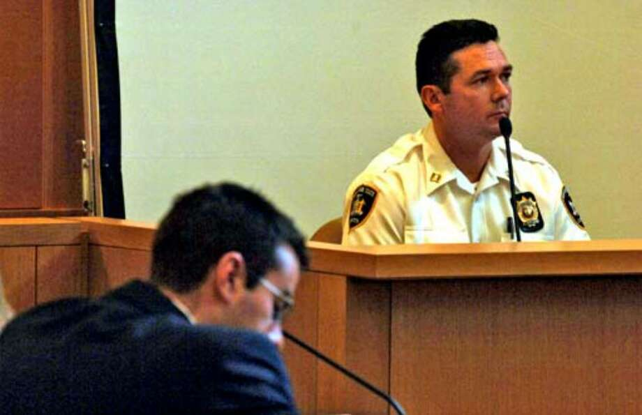 Court Officer Captain Michael Hart answers questions on the witness stand about arrving on the scene of the Porco murder and assault in November 2004. Defendant Christopher Porco is seated at left. Photo: Philip Kamrass