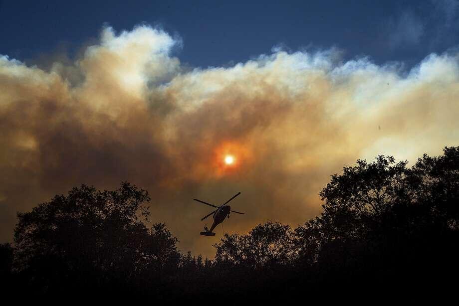 Smoke billows from the Camp Fire as a firefighting helicopter flies near Pulga, Calif., on Sunday, Nov. 11, 2018. (AP Photo/Noah Berger) Photo: Noah Berger / Associated Press