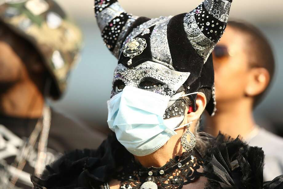 A fan wears a face mask in the stands during the NFL game between the Oakland Raiders and the Los Angeles Chargers at Oakland-Alameda County Coliseum on November 11, 2018 in Oakland, California. An Air Quality Advisory was issued due to heavy wildfire smoke in parts of the Bay Area from the Camp Fire in Butte County.  Photo: Ezra Shaw, Getty Images