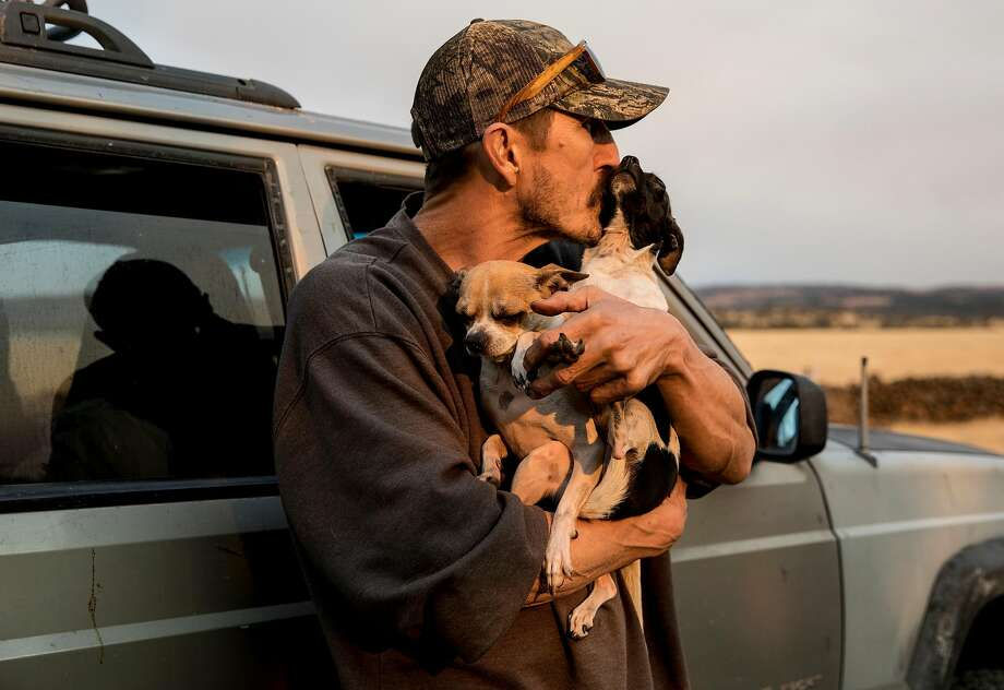 Greg Woodcox with his dogs, Romey and Jules, after recounting his narrow escape from the Camp Fire in Paradise. Photo: Jessica Christian / The Chronicle
