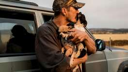 Greg Woodcox poses for a portrait with his dogs, Romey and Jules, after recounting his harrowing escape from Edgewood Lane from the Camp Fire in Paradise, Calif. while standing near his Jeep watching the fire from Chico Airport in Chico, Calif. Sunday, Nov. 11, 2018