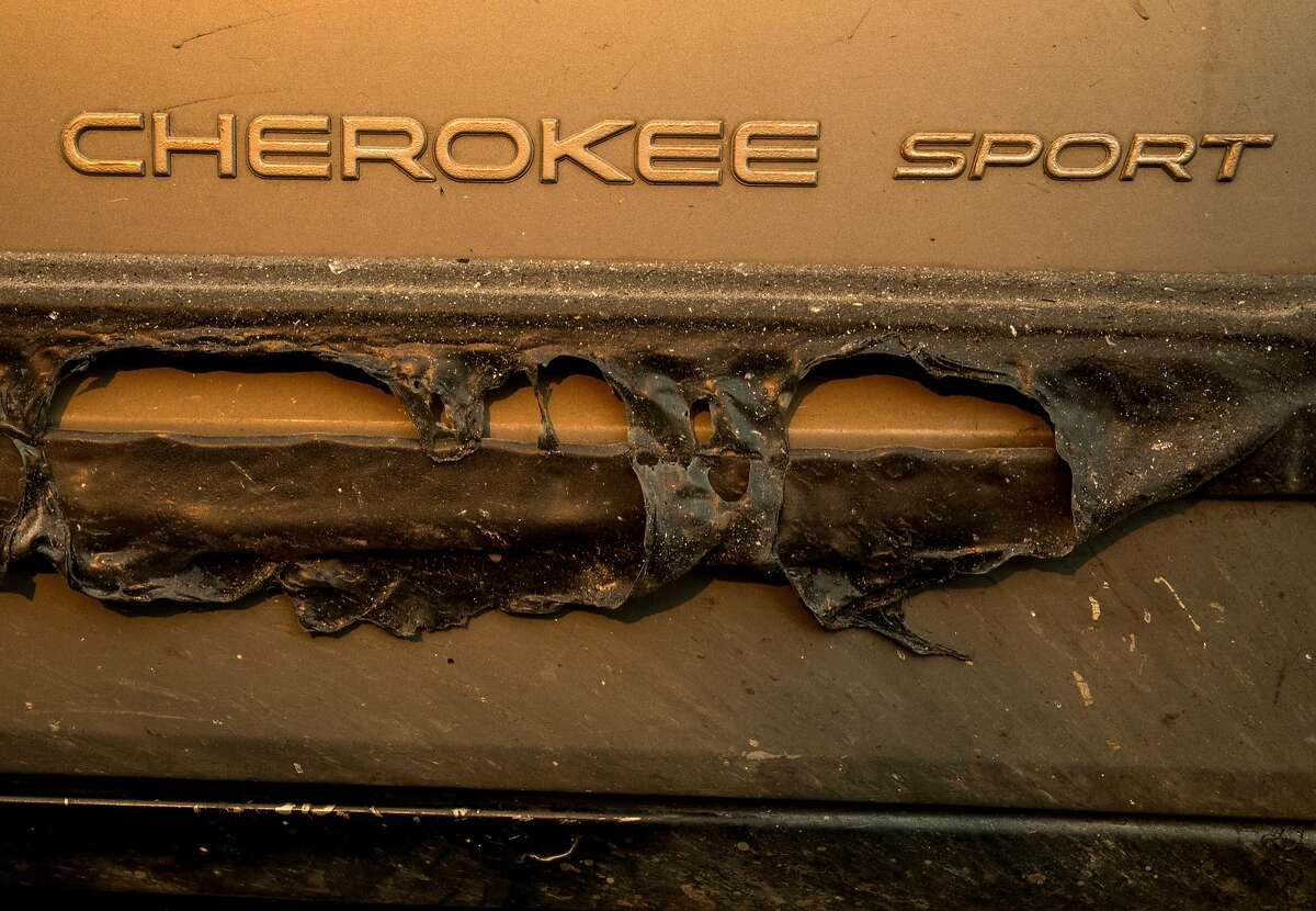The melted side pane of Greg Woodcox's Jeep Cherokee is seen as he recounts his harrowing escape from Edgewood Lane from the Camp Fire in Paradise, Calif. while sitting in his Jeep watching the fire from Chico Airport in Chico, Calif. Sunday, Nov. 11, 2018