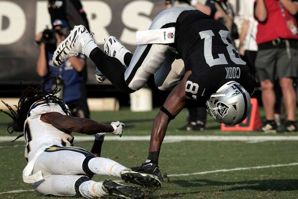 Jared Cook (87) is upended after a catch for a 31 yard gain in the second half as the Oakland Raiders play the Los Angeles Chargers at the Coliseum in Oakland, Calif., on Sunday, November 11, 2018.