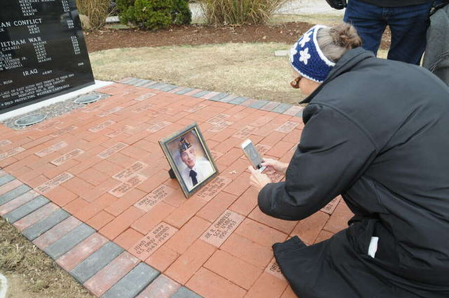 Sara Sladek takes a photo of her late mother Esther Rapp's World War II portrait next to her memorial brick at the East Alton Veterans Memorial on Sunday. Photo: David Blanchette | For The Telegraph