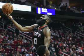Houston Rockets guard James Harden, top, drives to the basket over Indiana Pacers guard Victor Oladipo during the second half of an NBA basketball game, Sunday, Nov. 11, 2018, in Houston.