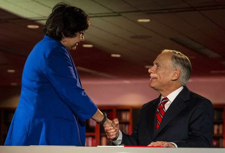 Texas Governor Greg Abbott, right, shakes hands with Lupe Valdez, his Democratic challenger, prior to a debate at the LBJ Library in Austin, Texas, on Friday, Sept. 28, 2018.