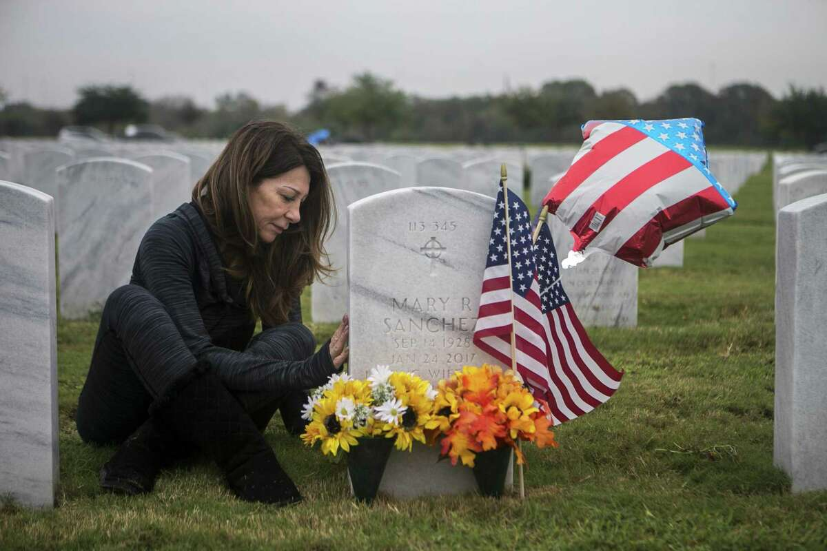 """Eva Sanchez gently touches the headstone of her father-in-law, Carlos Sanchez, and her mother-in-law, Mary Sanchez, as she visits their graves to decorate them at Fort Sam Houston National Cemetery on Nov. 11, 2018. Carlos Sanchez was an Air Force medic who fought in World War II. He and his wife had been together for about 63 years when Mary Sanchez died of dementia in January 2017. A year later, Carlos Sanchez died of """"a broken heart,"""" Eva Sanchez said."""