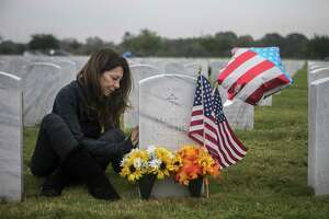 "Eva Sanchez gently touches the headstone of her father-in-law, Carlos Sanchez, and her mother-in-law, Mary Sanchez, as she visits their graves to decorate them at Fort Sam Houston National Cemetery on Nov. 11, 2018. Carlos Sanchez was an Air Force medic who fought in World War II. He and his wife had been together for about 63 years when Mary Sanchez died of dementia in January 2017. A year later, Carlos Sanchez died of ""a broken heart,"" Eva Sanchez said."