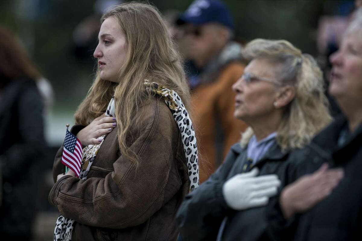 People attending the Veterans Day ceremony hold their hand over their hearts during the National Anthem on Sunday during at Fort Sam Houston National Cemetery Sunday. This year's observance of Veterans Day also marks a century since the end of World War I.