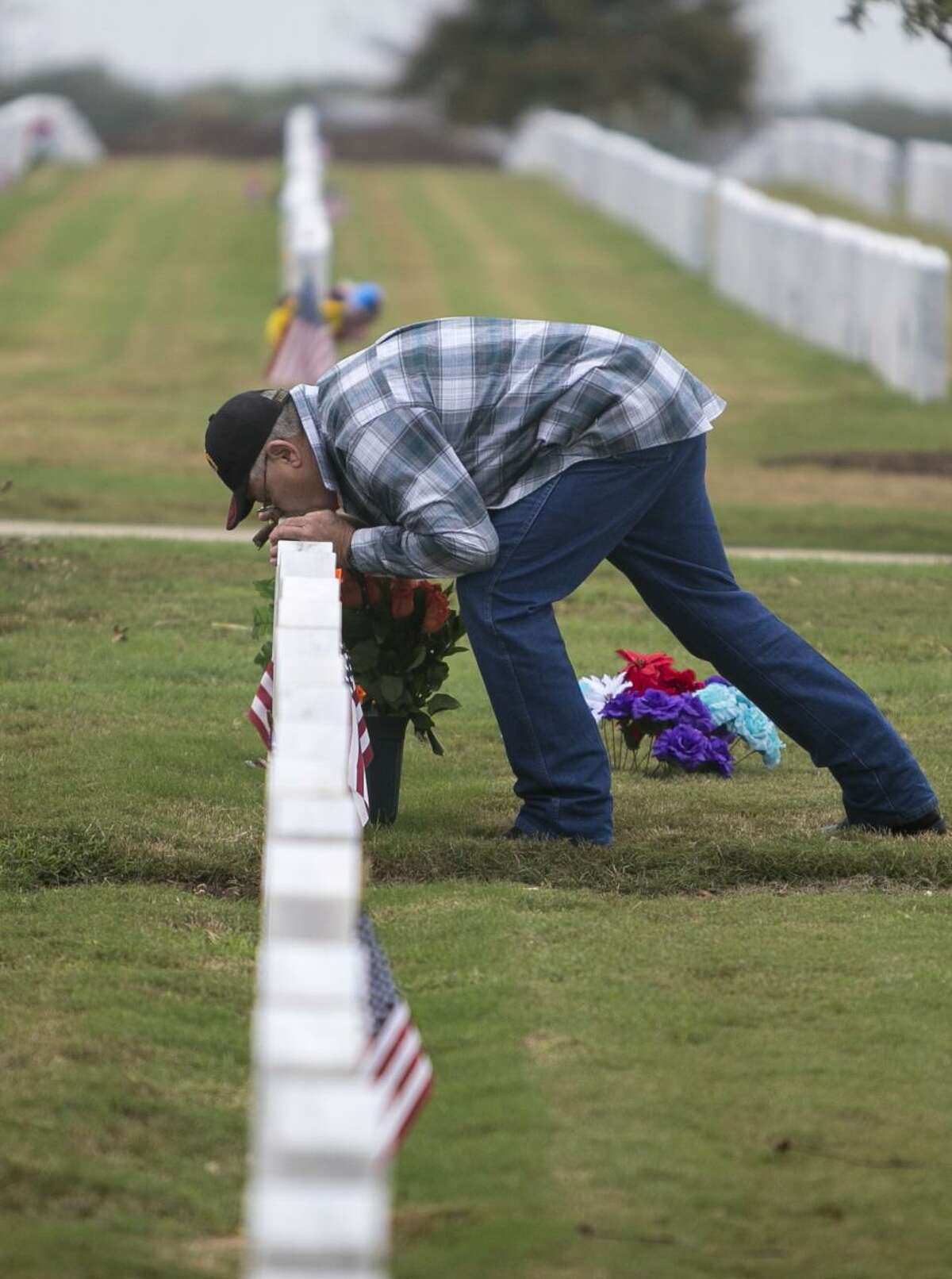 """Sam Allen bends over to kiss the headstone of his wife, Mary Allen, who died in March of this year. He visits her grave at Fort Sam Houston National Cemetery several times a week, and sometimes brings his guitar to sing to her. """"She was in the Army and I was a Marine - an unlikely couple but it worked,"""" Allen said on Nov. 11."""