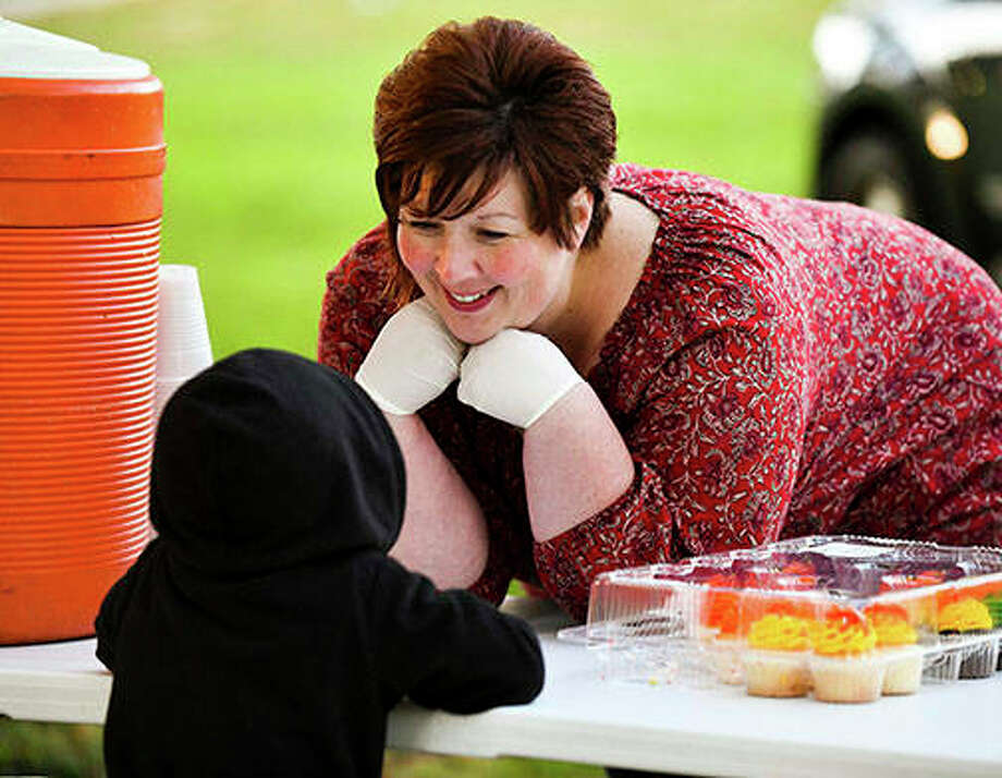 Nikki Leman of the Southside Community Center in Peoria chats with children as she serves food at Peoria's Harrison Homes. Photo: Ron Johnson | Journal Star (AP)