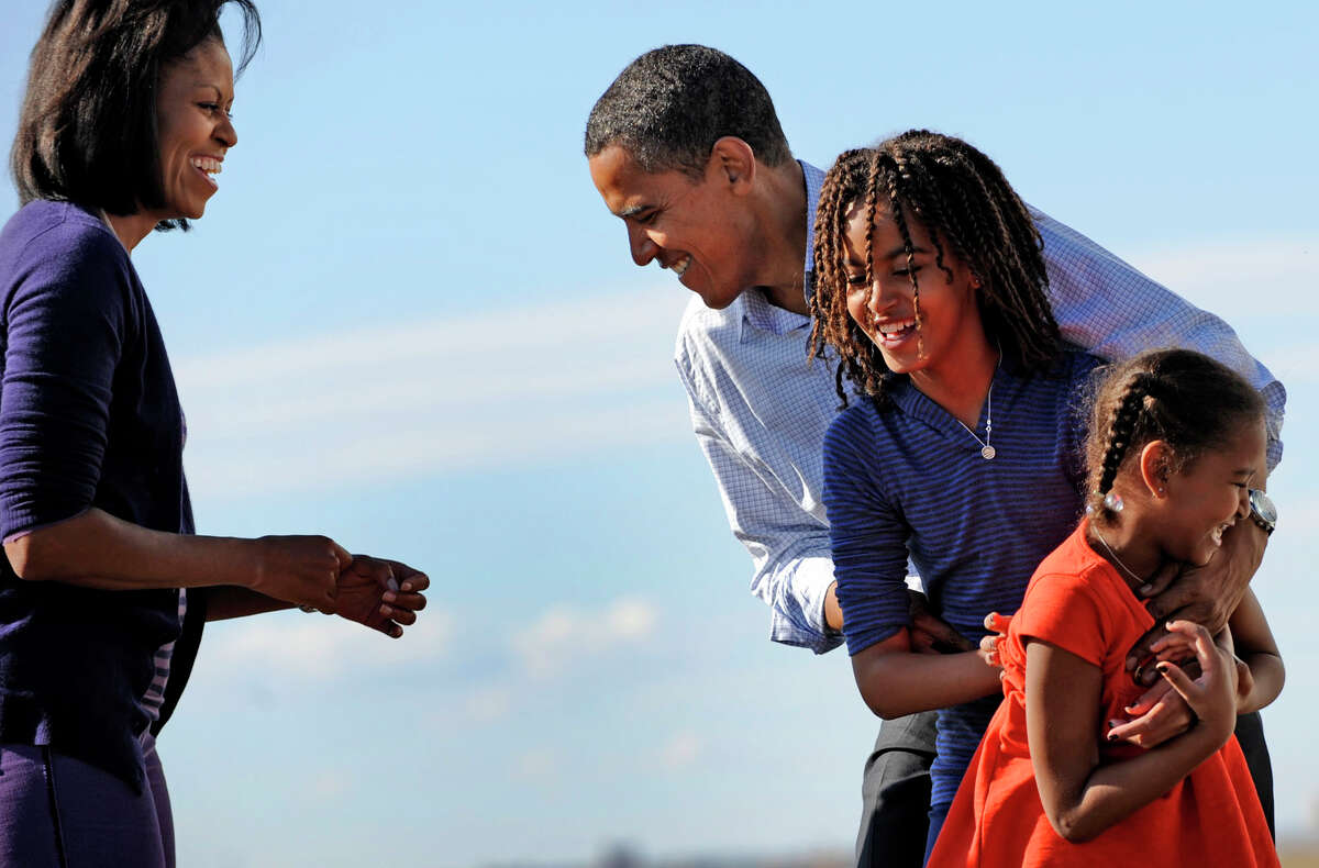 Michelle Obama and her daughters greet Barack Obama at a campaign stop in Colorado in 2008. In her memoir, she writes that she was a reluctant political spouse. (Linda Davidson/The Washington Post)
